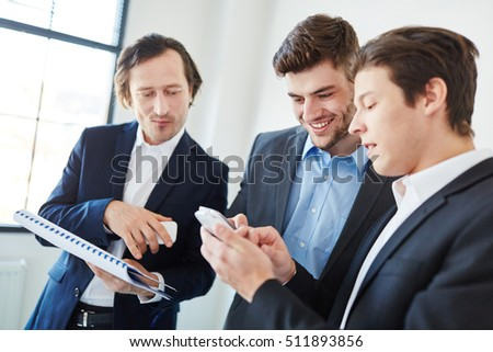 Business people reading SMS news in start-up