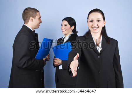 Business people relationship ,a businesswoman standing in front and saying welcome giving hand and others having a conversation in background and holding folders - stock photo