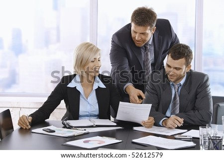 Business people reviewing documents in office, businessman pointing at paper, smiling. - stock photo
