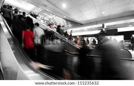 business people rushing on the escalator in motion blur on the subway station. - stock photo