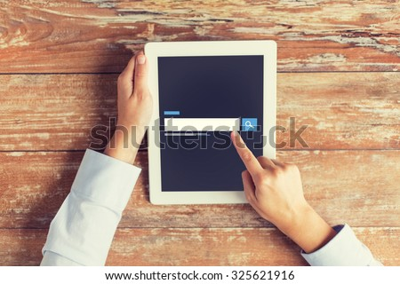 business, people, search, web and technology concept - close up of male hands using internet browser on tablet pc computer and coffee cup at table - stock photo