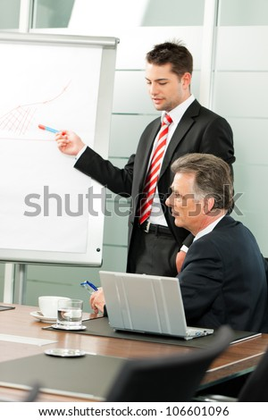Business people - Senior Manager or boss in meeting discussing new strategy while a male colleague is doing the presentation - stock photo