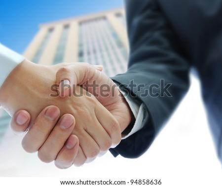 business people shaking hands  building background - stock photo