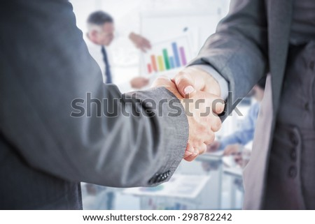 Business people shaking hands close up against business man giving a presentation - stock photo