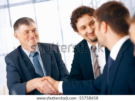 Business people shaking hands, coming to an agreement in the office.
