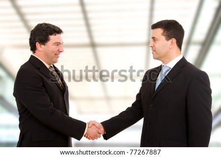 Business people shaking hands, finishing up a meeting at modern office bulding