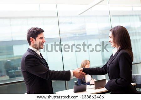 Business people shaking hands, finishing up a meeting at the office - stock photo