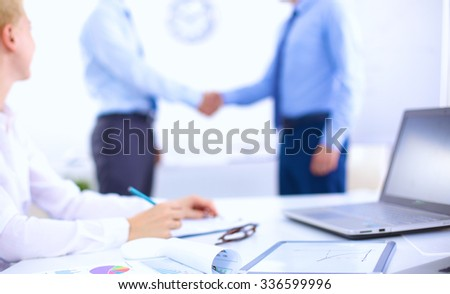 Business people shaking hands, finishing up a meeting, in office. blurred - stock photo