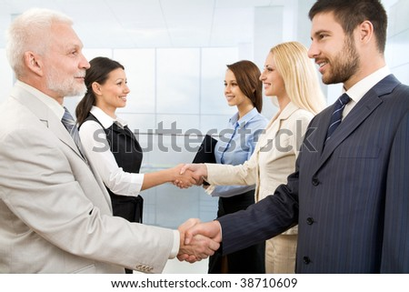 Business people shaking hands in a modern office - stock photo