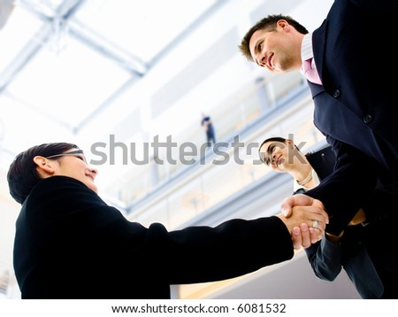 Business people shaking hands in the entrance hall of the office building. Selective focus is placed on the hands. - stock photo