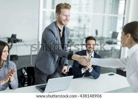 Business people shaking hands in the office after a job well done - stock photo