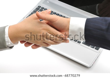Business people shaking hands over a laptop isolated on white background.