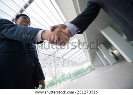 Business people shaking hands, view from below - stock photo