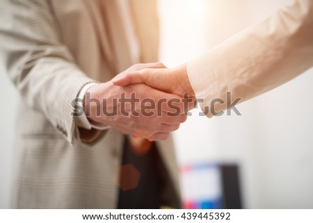 Business people shaking their hands. Lens flare effect - stock photo
