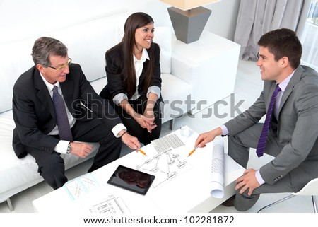 Business people sharing ideas at meeting with documents and tablet on table.