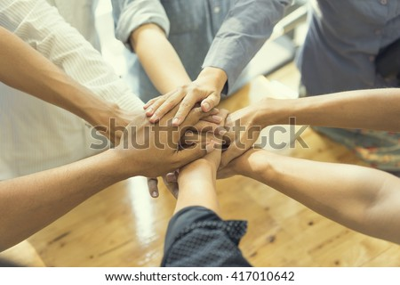 business people showing unity with their hands together, soft focus, vintage tone - stock photo