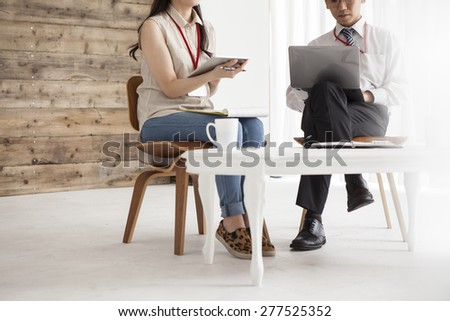 Business people sitting at table with papers and laptop and planning - stock photo