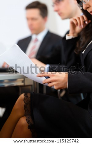 Business people sitting in a meeting or workshop in an office - stock photo