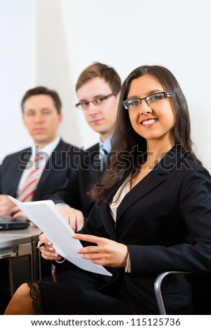 Business people sitting in a meeting or workshop in an office, they are looking into the camera - stock photo