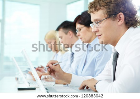 Business people sitting in a row and working - stock photo