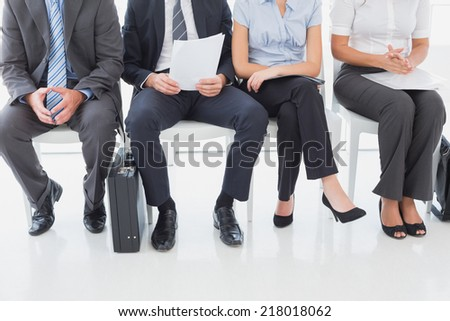 Business people sitting in a row in an office - stock photo