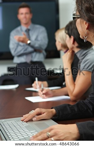 Business people sitting in a row on business training, focus on female hand typing notes on laptop. - stock photo