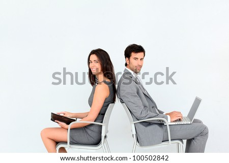 Business people sitting in chairs back to back - stock photo