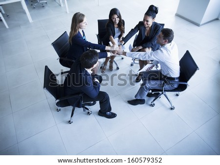 Business people sitting in circle with hands together cheering - stock photo