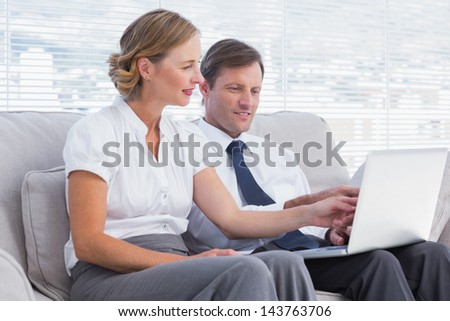 Business people sitting on couch watching something on laptop