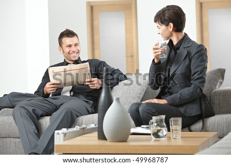Business people sitting on sofa at office anteroom waiting and talking - stock photo