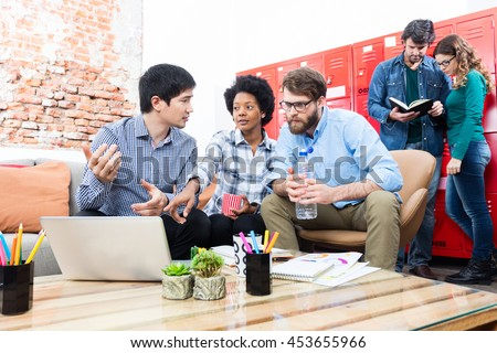 Business people sitting sofa creative office diverse mix race group businesspeople working discussing laptop computer - stock photo