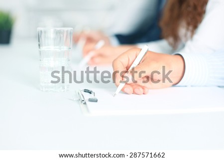 Business people sitting together and making notes at workplace - stock photo
