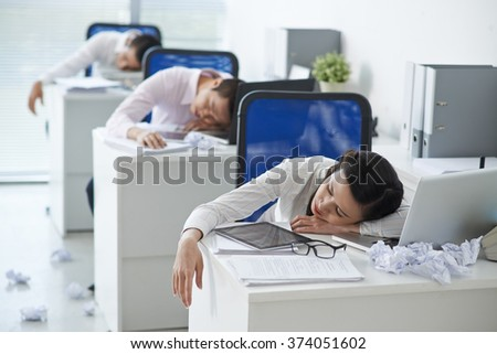 Business people sleeping at their workplaces