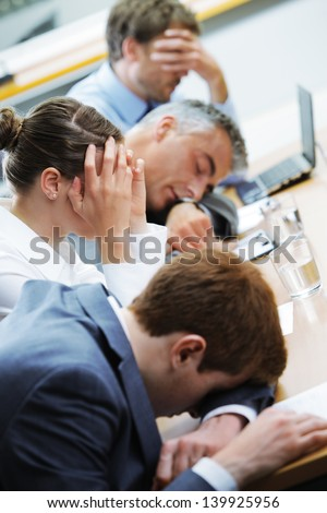 Business people sleeping in the conference room during a meeting, focus on woman - stock photo