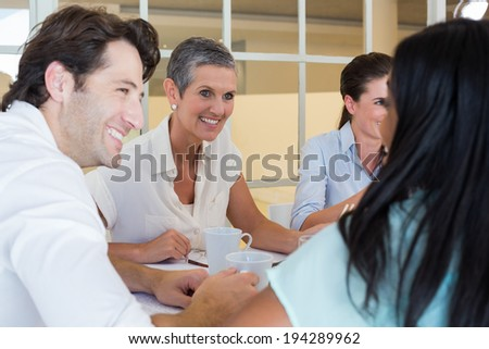 Business people smile and chat while enjoying hot drinks in the office - stock photo