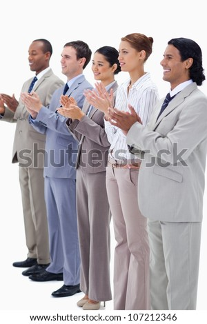 Business people smiling and applauding while looking towards the left side against white background - stock photo