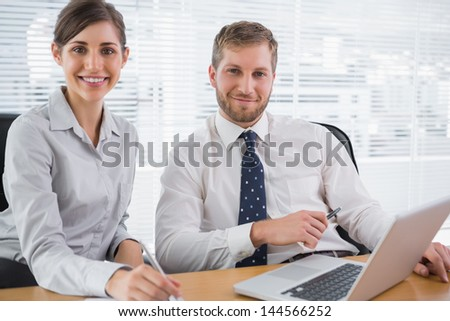 Business people smiling at camera with laptop sitting at desk in office - stock photo