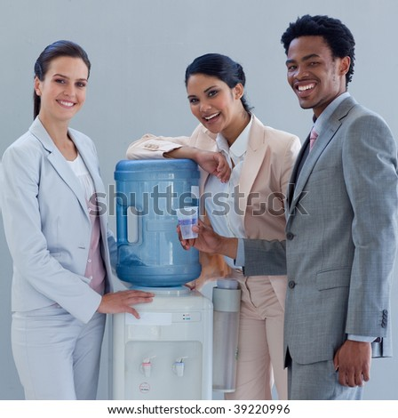 Business people smiling next to a water cooler in office - stock photo