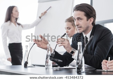 Business people speaking at presentation in microphone in office - stock photo