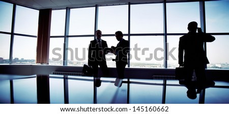 Business people spending a usual busy day in office, only silhouettes being recognizable