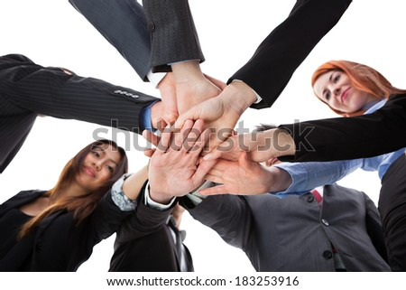 Business people stacking hands. Shot from below