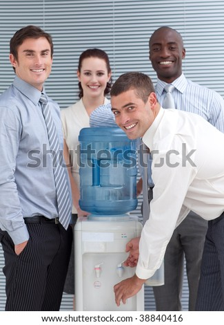 Business people standing around water cooler in workplace - stock photo