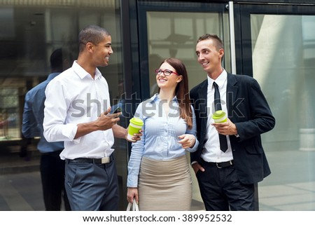Business people standing in front of their office, looking each other and smiling. Their are at coffee break. Shallow depth of field. - stock photo