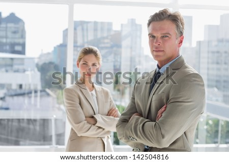 Business people standing together with arms crossed in a bright office - stock photo