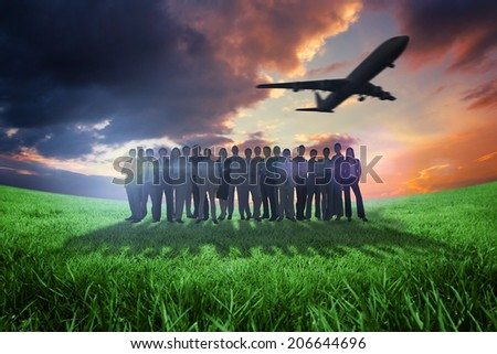 Business people standing up with airplane against green field under orange sky - stock photo
