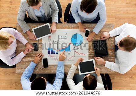 business, people, statistics and team work concept - close up of creative team with charts on paper, smartphones and tablet pc computers sitting at table in office - stock photo