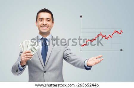 business, people, success and finances concept - smiling businessman with american dollar money and growing chart over gray background - stock photo