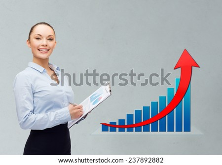 business, people, success  and statistics concept - young smiling businesswoman with clipboard and pen over gray background and growth chart