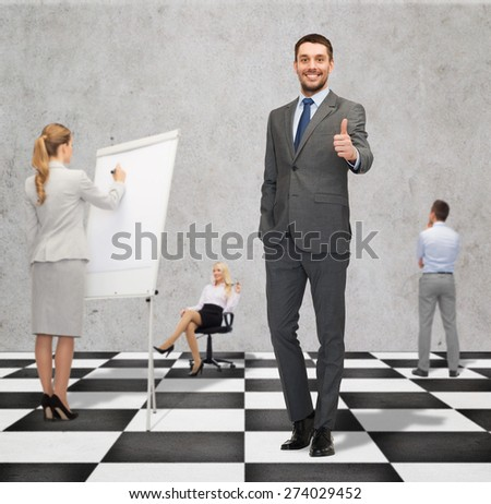 business, people, success, teamwork and strategy concept - smiling young businessman showing thumbs up gesture standing on checkerboard pattern floor over gray background and businesspeople - stock photo