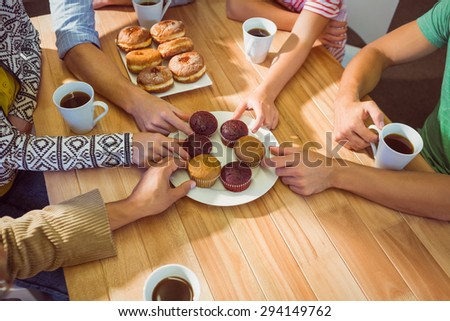 Business people taking cakes on table after lunch in the office - stock photo